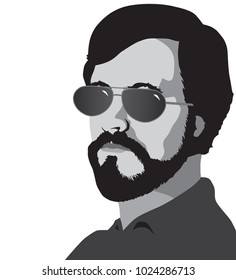 A bearded man in sunglasses is looking toward the viewer