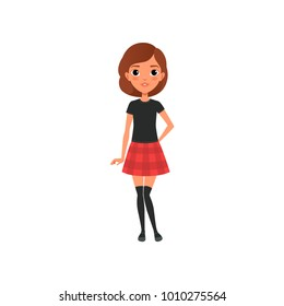 Beautiful brunette girl in stylish outfit black t-shirt, knee socks and red plaid mini skirt. Cartoon teenager character with big shiny eyes. Flat vector design