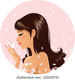 Beautiful girl smelling sakura flowers