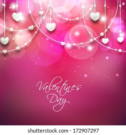 Beautiful Happy Valentines Day concept with hanging heart shapes on shiny pink background.