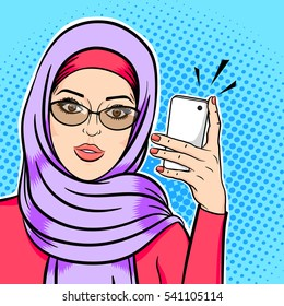 Beautiful modern muslim woman in hijab holding mobile phone reading sms or taking selfie concept vector in pop art comic retro style.