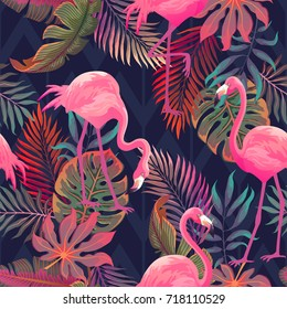 Beautiful seamless vector tropical pattern with pink flamingo and palm leaves on dark background. Abstract summer texture