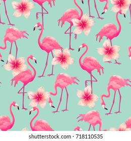 Beautiful seamless vector tropical pattern with pink flamingo and flowers on blue background. Abstract summer texture