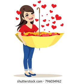 Beautiful young woman capturing falling red hearts rain with big yellow upside down umbrella love concept