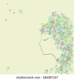 Beautiful young woman with flowers and leaves in her hair