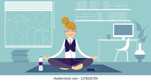 A Bespectacled yoga girl in headphones meditates in the office, sitting on a pilates mat in an easy sukhasana pose. Beside her a bottle of water and a computer on the table.