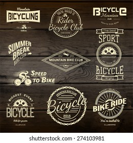 Bicycle set badges logos and labels for any use, on wooden background texture. EPS10