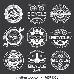 Bicycle shop or bike repair service set of vector white emblems, badges and labels on dark background
