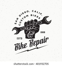 Bike Repair Abstract Vintage Vector Sign, Label or Logo Template. Fist Holding Wrench with Retro Typography and Shabby Textures. Isolated.
