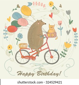 Birthday card with funny bear riding a bicycle with a cat and balloons. Cartoon watercolor style.