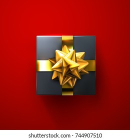 Black gift box with glittering golden bow and ribbons isolated on red background. Vector realistic festive illustration. Decoration element for holiday design. Top view