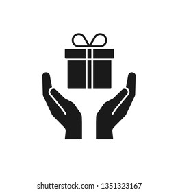 Black isolated icon of gift box in open hands on white background. Silhouette of gift box and two hands. Give, make a present.
