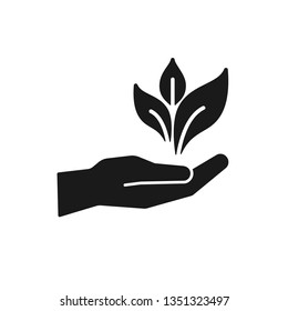 Black isolated icon of hand with leaf, plant on white background. Silhouette of hand with leaf. Bio, eco, gardening.
