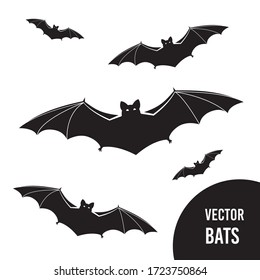 Black silhouettes of flying bats set on white background. Flittermouse night creatures. Flying black bats traditional Halloween symbols