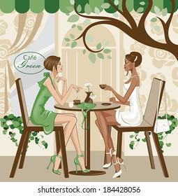 A black woman in white outfit and a white woman in green are sitting at a cafe, having a coffee