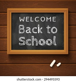 """Blackboard with text """"back to school"""" on wooden wall"""
