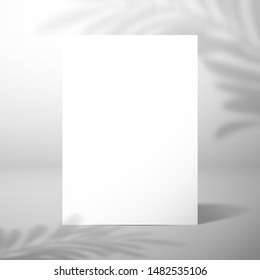 A  blank card or sheet of paper stands near a white wall with a shadow of a palm tree. Mockup for design