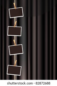 blank photo frames hanging from a clothes line on a black curtain