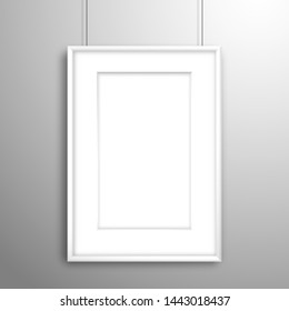 Blank white frame with passe-partout for an image or poster hanging on threads near the wall. Mockup for design with shadow
