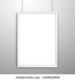 Blank white frame for a picture or poster hanging on strings near the wall. Mockup for design with shadow