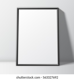 Blank white paper poster in thin black frame standing on floor. Poster mock-up template