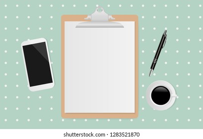 Blank white sheet on clipboard with coffee cup,pen and smartphone on polka dot green background