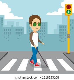 Blind man holding white cane walking pedestrian crossing with green traffic light
