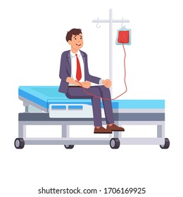Blood donor in a suit is sitting on the hospital bed, donating blood