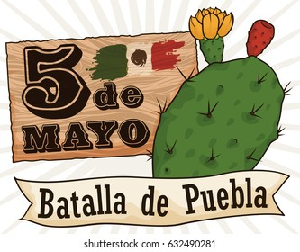 Bloomed nopal with tuna fruit, close to wooden sign with reminder of Puebla Battle in Cinco de Mayo (written in Spanish) and a ribbon.