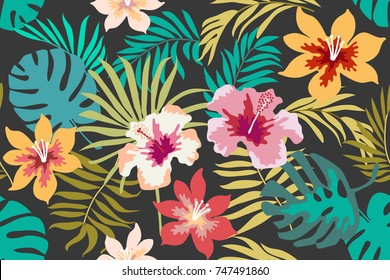Blooming tropical flowers and palm leaves on dark grey background. Seamless botanical pattern with aloha motifs. Trendy design for textile, cards and invitations.