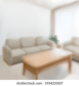 Blurred interior of living room with sofa set and wooden center table in 3D illustration