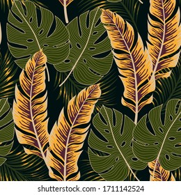 Botanical seamless tropical pattern with bright plants and leaves on a black background. Summer colorful hawaiian seamless pattern with tropical plants. Printing and textiles.