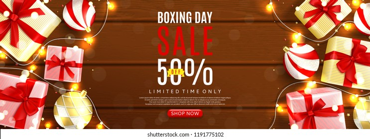 Boxing day sale web banner. Top view on realistic gift boxes and Christmas balls on rustic wooden texture. Vector illustration with confetti and effect bokeh.