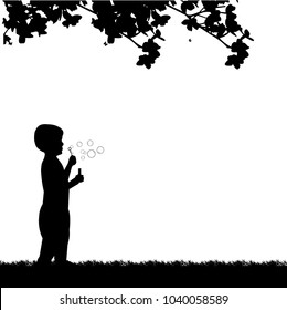Boy blowing soap bubbles in park in spring silhouette, one in the series of similar images