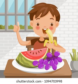 Boy eating fruit. sitting at the table eating Banana. Watermelon and grapes in a tray placed on a table at home in the dining room. emotional mood on child's face feels good. Symbols hand thumb up.