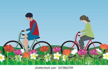 Boy and girl riding a bicycle through a meadow with flowers