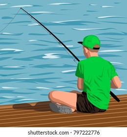 Boy in the green shirt and black shorts is sitting on the dock with a fishing rod. Fishing from the pier into the sea or a river shore