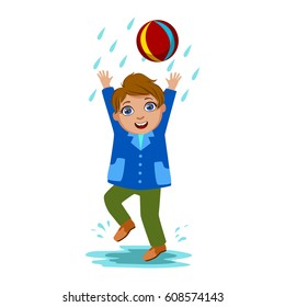 Boy Playing With The Ball, Kid In Autumn Clothes In Fall Season Enjoyingn Rain And Rainy Weather, Splashes And Puddles