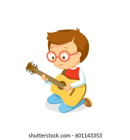 Boy playing guitar. Boy plays an acoustic guitar. Learning to play acoustic guitar for children.