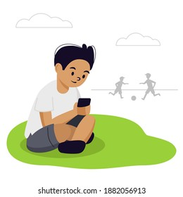The boy is sitting on the grass in the park. He looks at his phone. His friends are playing football. He has a smartphone addiction, he does not play with them