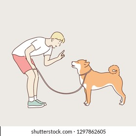 A boy is training a dog. hand drawn style vector design illustrations.