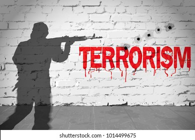 Brick wall bearing the legend terrorism and bullet markings with shadow of a man with a riffle, conceptual illustration.