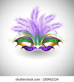 Bright Mardi Gras mask with purple and green feathers, decorated with gold pattern on light background.