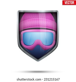 Bright metallic shield in the winter cap and ski goggles inside. Editable Vector Illustration isolated on white background.