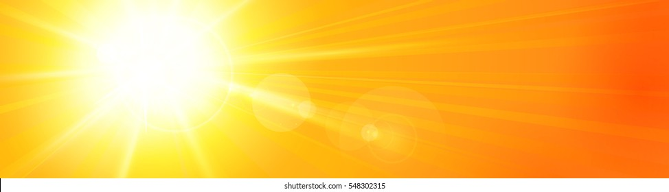 Bright sun left of the sky with sun rays and a lens flare in a vividly orange yellow sky. Panorama view for header, footer, or banner. Copy space