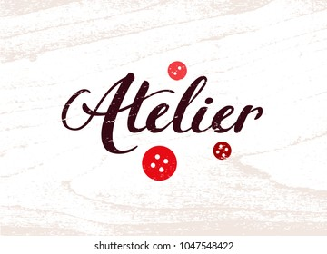 "Brown retro calligraphy logo of Atelier with bright red buttons on white wooden background. Template of banner for seamstress. Hand drawn lettering word ""Atelier"" with flat icons of buttons."