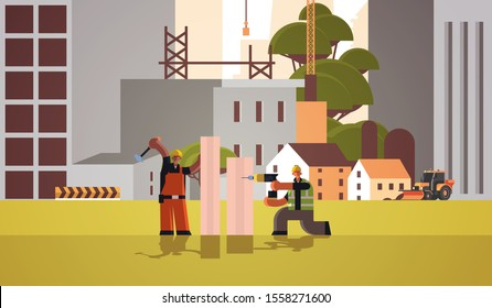 builders couple using drill and hummer mix race workmen carpenters team drilling hole hammering nail in wooden plank building concept construction site background full length horizontal vector