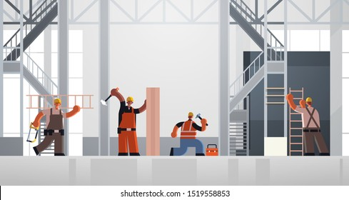 builders using hammer and ladder busy workmen carpenters team in uniform working together building concept construction site interior flat full length horizontal