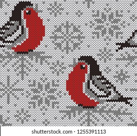Bullfinch jacquard knitted seamless pattern. Winter snowy background with cute birds and snowflakes. Northern style. Vector illustration.