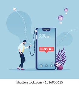 Businessman chained and shackled to a big smart phone-social networks addiction metaphor
